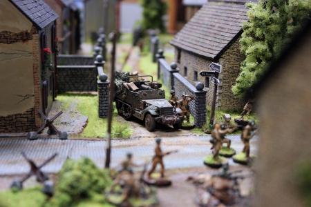 Ein amerikanische Halbkettenfahrzeug mit abgesessener Infanterie am zentral gelegenen Bauernhof.